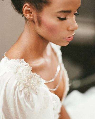 Closeup of African American bride with makeup and updo bridal hairstyle by Beauty on Location Studio of Denver, Colorado