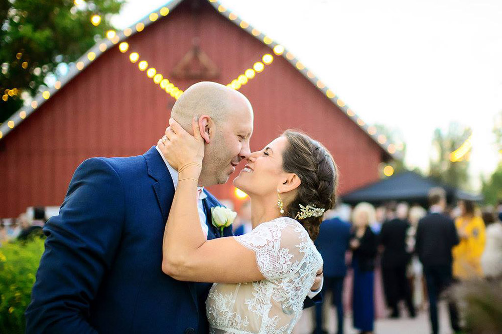 Bride and groom embracing in front of barn at a rustic ranch style wedding